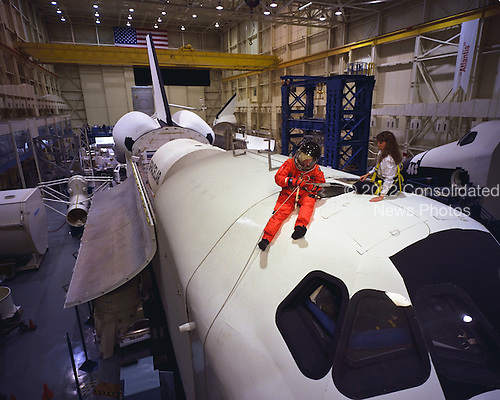 United States Senator John H. Glenn Jr. (Democrat of Ohio), talks with crew trainer Sharon Jones prior to simulating procedures for egressing from a troubled Space Shuttle at the Johnson Space Center in Houston, Texas on April 28, 1998. This training mockup is called the full fuselage trainer (FFT). Glenn has been named as a payload specialist for STS-95, scheduled for launch later this year. Photo Credit: Joe McNally, National Geographic / NASA via CNP