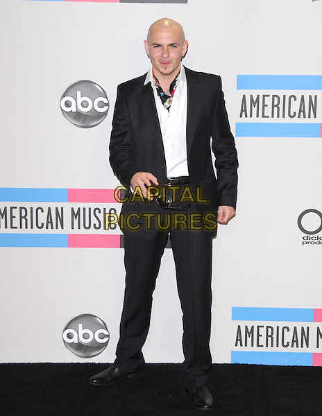 PITBULL (Armando Christian Perez).at The 2010 American Music  Awards held at Nokia Theatre L.A. Live in Los Angeles, California USA, .November 21st 2010..AMAs Pressroom   press full length black jacket white shirt suit scarf .CAP/RKE/DVS.©DVS/RockinExposures/Capital Pictures.