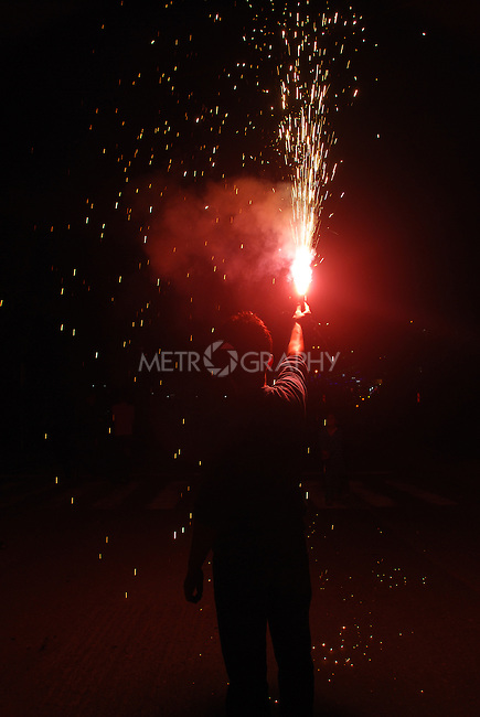 DOHUK, IRAQ:  A man sets off a firework during Newroz celebrations...Newroz, celebrated across the world on the vernal equinox, is the official beginning of the Kurdish calendar and the first day of spring.  Kurds celebrate Newroz on March 20th and 21st by lighting fires and performing traditional dances...Photo by Ari Jalal/ Metrography