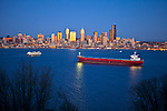Seattle, Washington<br /> Dusk on Elliott Bay with red container ship and passing ferry boat with Seattle city skyline glowing in reflected light
