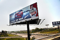 A Mitsubishi billboard featuring Jackie Chan stands above a freeway outside of Nanjing, China.