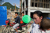 Farmers drive and walk past a construction site built over farmland in southwestern China.<br /> <br /> Communist leaders are pushing ahead with a gigantic, historic plan to uproot 100 million farmers and turn their fields into urban dwellings by year 2020 to create a giant new middle class and boost demand.