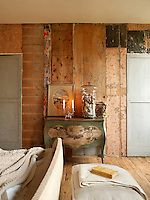 A bedroom with a feature wall composed of bare wood panels. Lighted candles and a glass jar stand on a French painted cabinet.