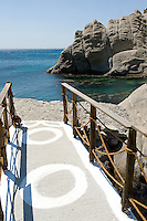 A concrete walkway with rustic balustrade leads down to a pebbled beach in a sheltered cove