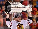Chicago Blackhawks center Andrew Shaw hoists the Stanley Cup after the Blackhawks defeated the Boston Bruins in the NHL hockey Stanley Cup Finals at TD Garden on Monday, June 24, 2013.