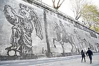 """Roma 12-04-2016 La serie di Murales più' lunga che sia mai stata realizzata a Roma, dal titolo, """"Triumphs and Laments"""", e' appena stata terminata dall'artista sudafricano William Kentridge, lungo i muraglioni del Tevere, tra Ponte Sisto e Ponte Mazzini. La tecnica, del tutto innovativa, ecologica e non invasiva, si basa semplicemente sul 'togliere' la patina di smog che il tempo ed il traffico cittadino hanno steso sui muraglioni, con del vapore. Il murale, lungo 550 metri, con 80 figure alte fino a 10 metri, narra la storia, fatta appunto di trionfi e lamenti, di Roma, e vi sono raffigurati momenti ed icone importanti per la storia della citta'. La Lupa capitolina, il trionfo di Cesare, la Vittoria alata, integra e spezzata, Marcello Mastroianni e Anita Ekberg nella Fontana di Trevi per la Dolce vita, Santa Teresa, Michelangelo, la morte di Remo accostata a quella di Pasolini, incluso un mega Mussolini a cavallo, affiancato dalla mano tesa del tipico saluto romano.<br /> <br /> Rome 12th April 2016. The longest series of murals in Rome was just ended along the river Tiber by the South African artist William Kentridge, titled """"Triumphs and Laments"""". The artist used a very simple, ecologic technique to realize the paintings: he 'cleaned' the layer of smog covering the walls along the river with vapor. The mural, 550mt long and made of 80 figures 10mt tall, tells the story, made of Triumphs and Laments, of Rome. From the bitch, symbol of the city, to the Thriumph of Juluis Caesar, from the winged victory to Marcello Mastroianni and Anita Ekberg in 'La dolce vita', from the killing of Pasolini to Mussolini.<br /> Photo Samantha Zucchi Insidefoto"""