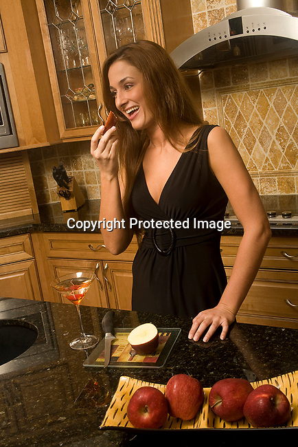 A young woman in her kitchen preparing snacks for a cocktail party.