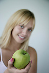 Portrait of a young woman holding a granny smith apple and smiling