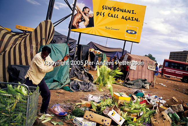 SOWETO, SOUTH AFRICA MARCH 8: An unidentified man throws garbage on the street on March 8, 2005 in Soweto, Johannesburg, South Africa. The man, a trader, sells corn by Baragwanath hospital, the main transport hub in the township. Soweto is South Africa?s largest township and it was founded about one hundred years to make housing available for black people south west of downtown Johannesburg. The estimated population is between 2-3 million. Many key events during the Apartheid struggle unfolded here and the most known is the student uprisings in June 1976, where thousands of students took to the streets to protest that they had to study the Afrikaans language at school. Soweto today is a mix of old housing and newly constructed townhouses, and a new hungry black middle-class is growing steadily. Most residents work in Johannesburg but the last years many shopping malls has been built, and people are starting to spend their money in Soweto.  .(Photo by Per-Anders Pettersson/Getty Images)..