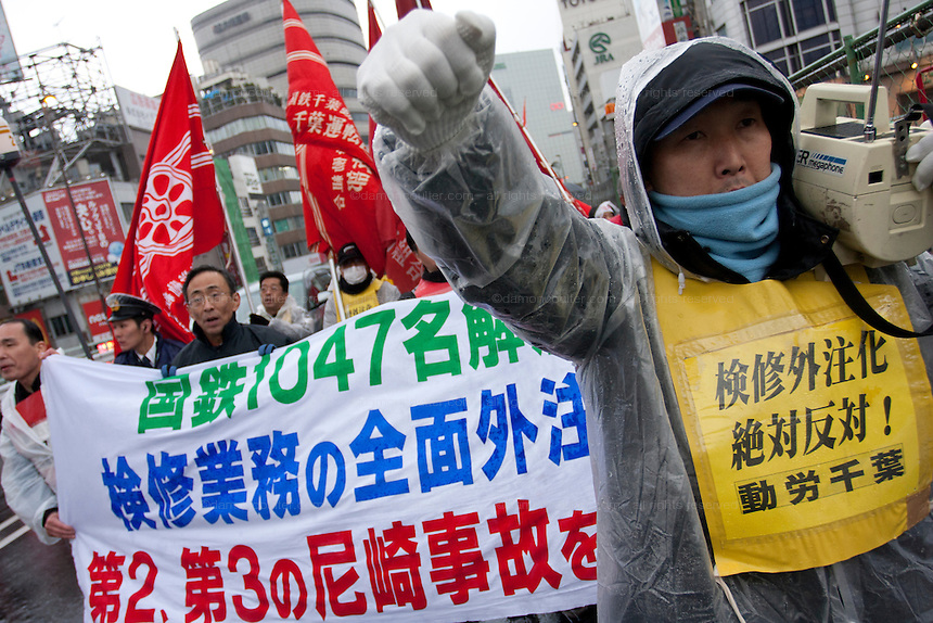 A marcher with a loudhailer followed by Yasahiro Tanaka, President of Dora Chiba railway Union lead a demo rally organized by Doro Chiba labour union to protest the outsourcing of what they consider essential safety and repair work and fight against rationalization of JR (Japan Railways) business. They also protested for the reinstatement of 1,047 national railway workers who lost their jobs in 1987. Shinjuku, Tokyo, Japan Saturday, February 13th 2010