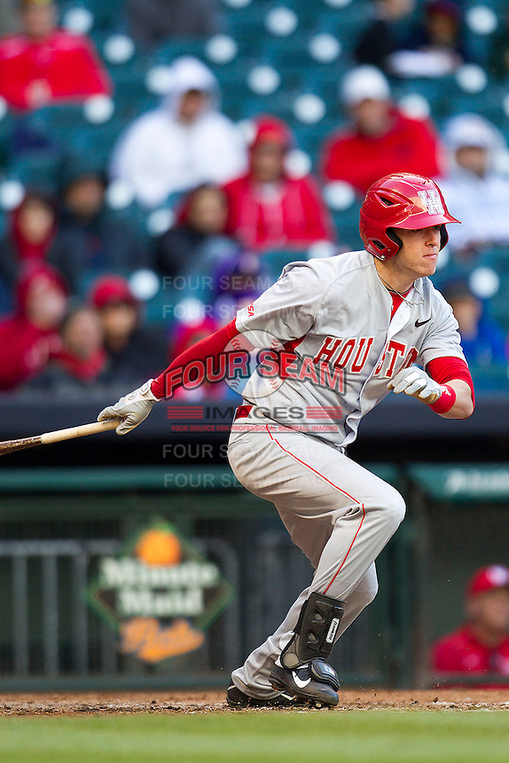 Houston Cougars outfielder Kyle Survance #34 follows through on his swing against the Baylor Bears in the NCAA baseball game on March 2, 2013 at Minute Maid Park in Houston, Texas. Houston defeated Baylor 15-4. (Andrew Woolley/Four Seam Images).