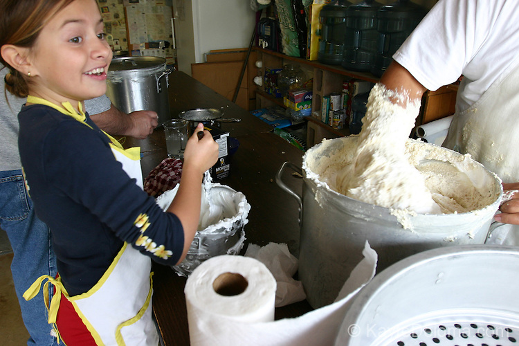 Mexican/Italian girl stirs shortening for the cornmeal masa at a family Tamalada (tamale making party), Torrance, CA