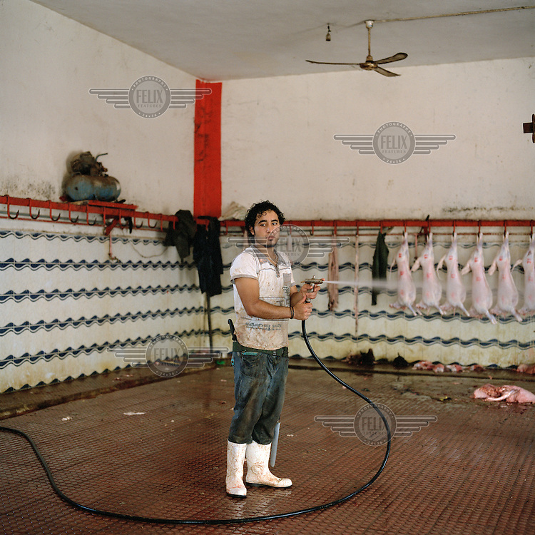 A young man who works at a slaughterhouse in Benghazi hoses down the floor after a busy morning's work.