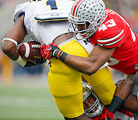 Ohio State Buckeyes defensive back Vonn Bell (11) and Ohio State Buckeyes linebacker Darron Lee (43) take down Michigan Wolverines wide receiver Devin Funchess (1) after a catch in the 1st quarter of their game at Ohio Stadium in Columbus, Ohio on November 29, 2014.  (Dispatch photo by Kyle Robertson)