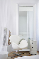 An Arne Jacobsen white leather Swan chair stands in front of a floor standing mirror with an Anna Castelli side table.