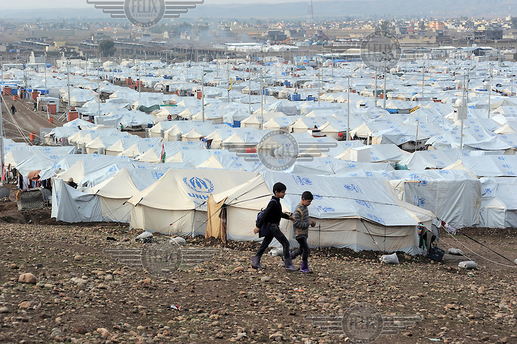 Two boys return from school to their family tents at the Kawergosk Syrian Refugee Camp.
