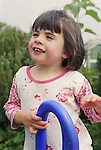 Young girl with autism standing at top of slide in garden smiling.  MR