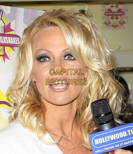 PAMELA ANDERSON .Pamela Anderson Celebrates Her All-Vegan Shake At Millions Of Milkshakes held At Millions Of Milkshakes, West Hollywood, California, USA, .9th April 2010. .portrait headshot white  v-neck make-up  microphone interview mouth open funny talking eyeshadow .CAP/ADM/KB.©Kevan Brooks/AdMedia/Capital Pictures.