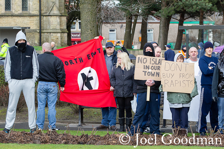 "© Joel Goodman - 07973 332324 . 03/03/2012 . Heywood , UK . Protesters hold up a National Front flag and placards reading "" No Islam in our town "" and "" Don't buy from rapists "" . The National Front hold a rally in protest against an alleged paedophile ring that had been operating in the area . There is currently (3rd March 2012) a case being tried at Liverpool Crown Court in relation to the allegations . Last Thursday (23rd February 2012) a protest organised in the town in relation to the same story resulted in Asian business being attacked by an angry mob . Photo credit : Joel Goodman"