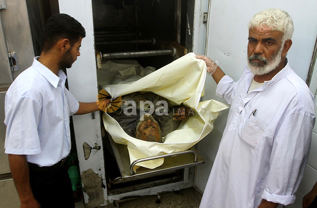Palestinians gather around the body of Ismail Amum ,65, at Al-Aqsa hospital morgue in the central Gaza Strip on August 24,2011. Israeli air strikes killed a local commander of the Islamic Jihad militant group in the Gaza Strip and wounded two militants who launched rockets at Israel, despite a two-day-old truce. Palestinian medics said the militant died when his car exploded as a result of the strike. Two other people were wounded. A separate Israeli strike wounded two other gunmen who were launching rockets at Israel. Photo by Ashraf Amra