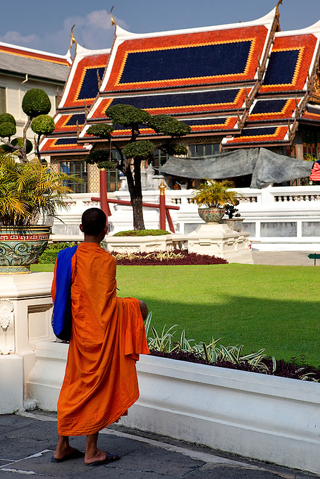 A monk pauses to absorb the beauty at Phra Borom Maha Ratcha Wang, Bangkok.