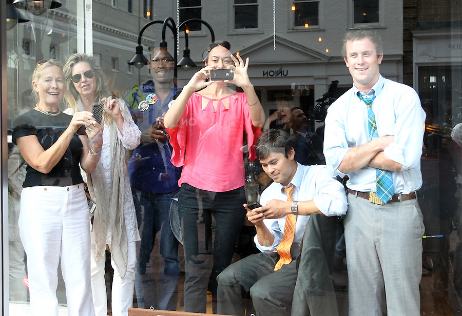 Supporters including Sissy Spacek (behind on right) watch through a store front window as President Barack Obama made a surprise stop to his campaign headquarters on the Downtown Mall in Charlottesville, VA.