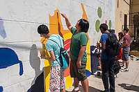 Volunteers gather on Brook Avenue in the Melrose neighborhood of the Bronx in New York on Saturday, August 9, 2014 to paint a mural about police violence and community safety. Designed by the artist Raul Ayala the painting project was organized by the Justice Committee, Caav: Organizing Asian Communities and Streetwise & Safe.  (© Richard B. Levine)