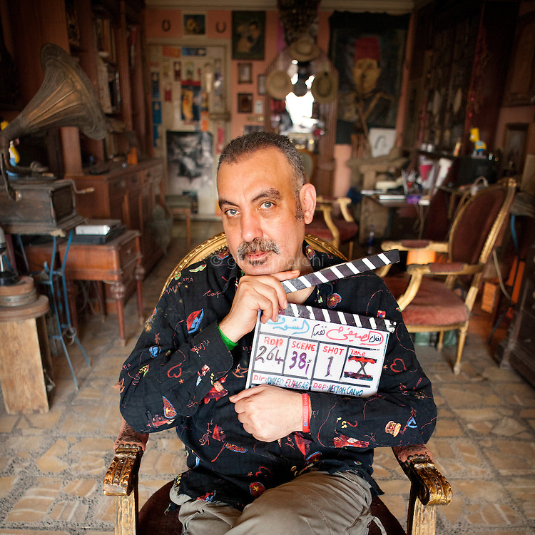 Egypt / Cairo / 2.4.2013 / Khaled El Hagar, Egyptian film director, poses in his house in Giza, holding the clapboard of his last film, El Shooq (Lust, 2010). © Giulia Marchi
