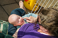 A mother, sitting in a garden swing seat,  strokes her baby's cheek as he has a break from breastfeeding.<br /> <br /> Taken - 27/04/2011<br /> Hampshire, England, UK