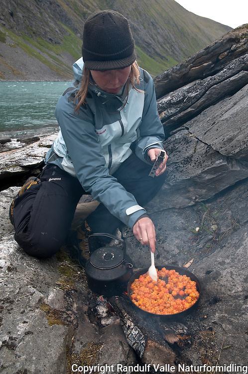 Dame lager mat på bål. --- Woman cooking on camp fire.