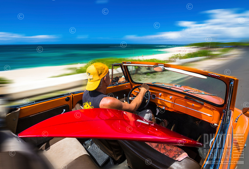 A blur motion image of man with a red surfboard driving a classic VW Bug by a beach along O'ahu's North Shore.