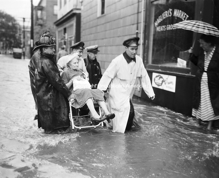 """Mrs. Margaret Garbukas of North Leonard Street is carried to safety the morning of """"Black Friday."""" Motor patrolman Joseph Murphy leads the group of rescuers. Fire Battalion Chief John Norton is at the rear."""