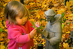 Toddler with statue of St. Francis in autumn.