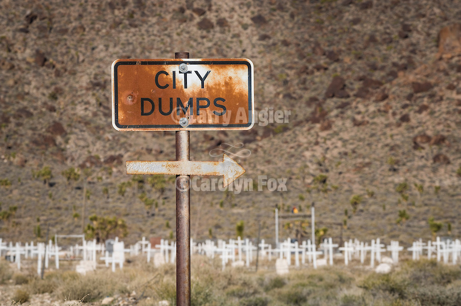 Rusting sign for the City Dumps with right-pointing arrow by the historic cemetery.