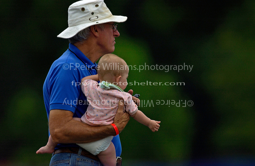 Fred Miller times son Gordy while holding his granddaughter.   (SST-120)