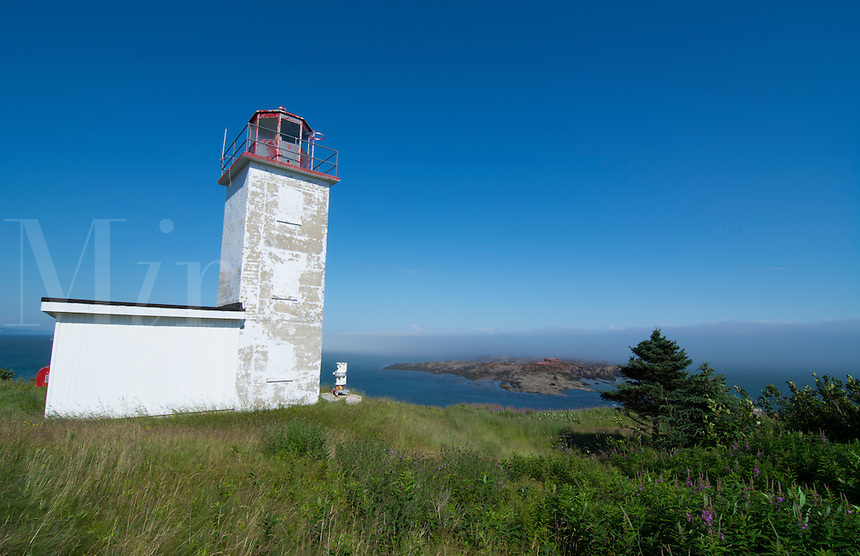 Canada St Martins New Brunswick white old traditional historic lighthouse ion water with fields on cliff