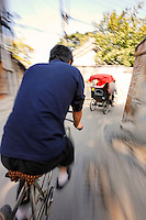 A pedicab driver follows another a rickshaw through a Beijing hutong, Beijing, China, Asia