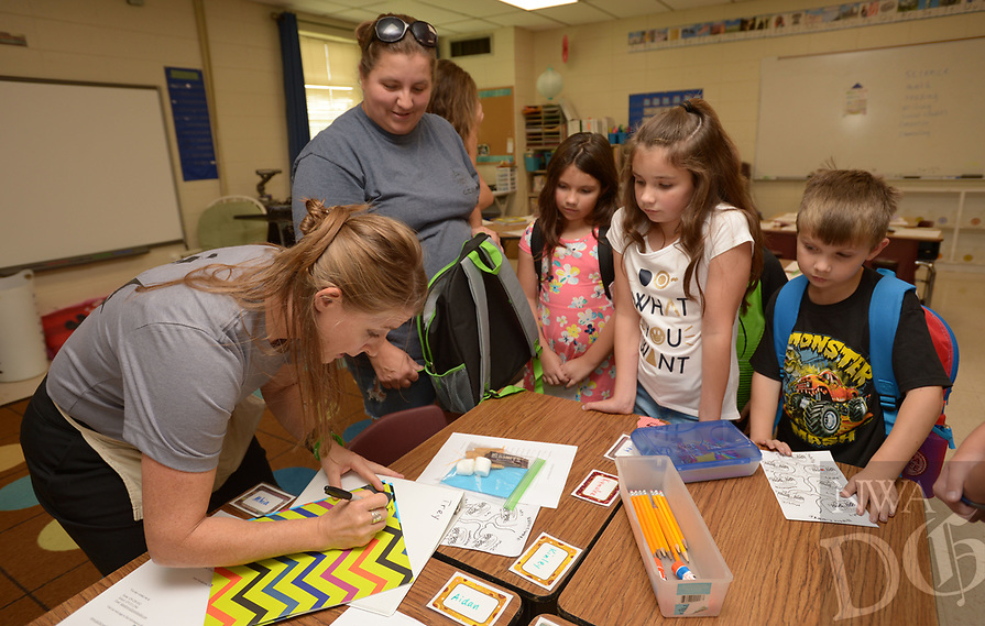 NWA Democrat-Gazette/ANDY SHUPE<br /> Amy Henderson (left), a second-grade reading teacher at Greenland Elementary School, helps Christina Vaughan (from left) and her children Bella, 8; Ally, 10; and Caiden, 6; Thursday, Aug. 9, 2018, during an open house at the school. Henderson was preparing Vaughan's son Trey for his first day of school. The district starts new teachers with a bachelor's degree at $34,513, one of five Northwest Arkansas school districts that start new teachers at $35,000 or less.