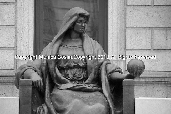 Statue of a woman holding a sphere in front of the Public Library in Boston, MA.