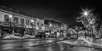 A snowy black and white view of part of downtown Oakville at night.