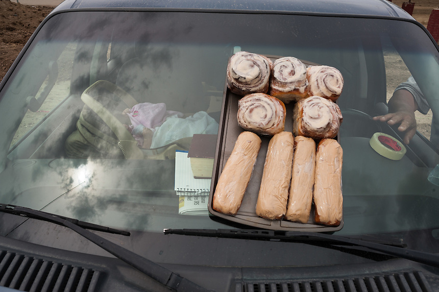 As granddaughter Persephone Old Bear, three months, rests on the passenger seat, John Enick, right, reaches for a roll of tape to secure his sign as his hommade maple bars and cinnamon rolls await buyer on the Crow Reservation at Crow Agency, Montana, Thursday, May 16, 2013. Pending new ports for shipment to Asia through either the U.S. or Canada, Cloud Peak Energey hopes to open new high-grade coal mines on and near the Crow Reservation in southern Montana. The tribe is equally hopeful the new mines would bring long-awaited economic stability to the tribe. (Kevin Moloney for the New York Times)