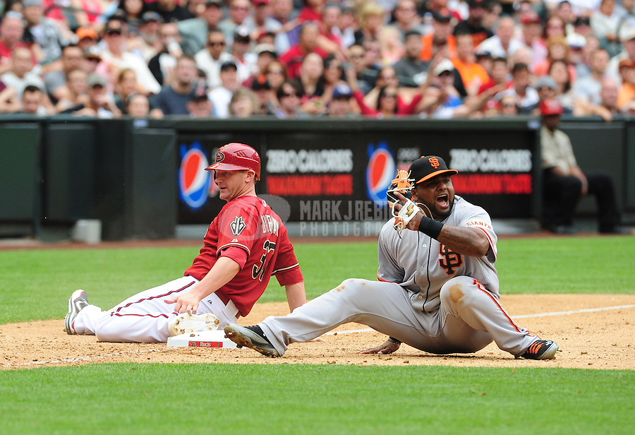 Apr. 8, 2012; Phoenix, AZ, USA; San Francisco Giants third baseman Pablo Sandoval (right) reacts after Arizona Diamondbacks base runner Lyle Overbay was called safe at third in the eighth inning at Chase Field. Mandatory Credit: Mark J. Rebilas-