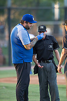 AZL Dodgers trainer Jesse Guffey applies pressure to home plate umpire Josh Williams' bloody nose during an Arizona League game against the AZL White Sox at Camelback Ranch on July 3, 2018 in Glendale, Arizona. The AZL Dodgers defeated the AZL White Sox by a score of 10-5. (Zachary Lucy/Four Seam Images)