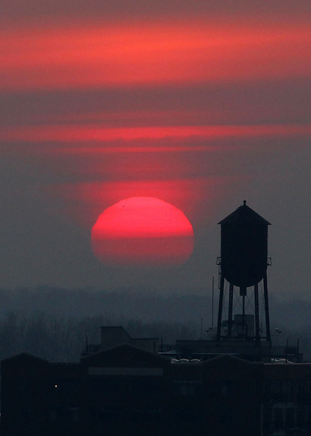 The sun sets behind a water tower atop the Brown-Camp Lofts in Des Moines.