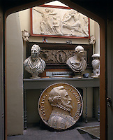 A small landing can be seen through a doorway where a collection of busts and bas-reliefs is displayed