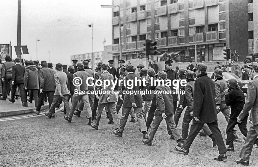 What is believed to be the Ulster Defence Association's first public appearance, since its formation in September 1971, passes Unity Flats, Peter's Hill, Belfast, Saturday 18th March 1972, on its way to the Shankill Road, a loyalist heartland. The predominently Roman Catholic occupied Unity Flats situated on the fringes of Loyalist West Belfast was a sectarian flash point for many years. 197203180342a. <br />