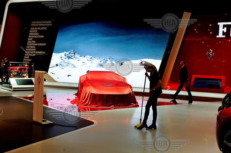 A woman cleans the floor around the New model Ferrari, kept under wraps prior to launching at the Geneva Motor Show.