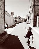 FRANCE, Burgundy, boy playing with soccer ball in street, Buffon (B&W)