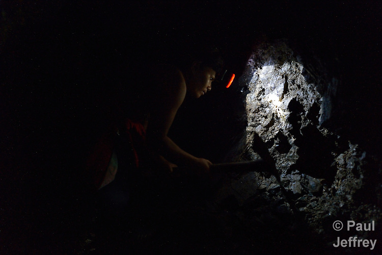Josephine Caderao, 39, searches for gold deep inside a small scale mine she operates with her husband in the Diwalwal area on the Philippines' southern island of Mindanao. Hers is one of several mining families fighting back against plans to displace them by the Philippine Mining Development Corporation, a front company for foreign mining companies that seeks to install a large-scale open pit gold mine in the area, also known as Mt. Diwata. The small miners were given notice to evacuate the area by June 5 or risk being forcibly removed by the military, which Caderao says harassed and interrogated her in June, 2011. The miners have defiantly refused to leave, and formed a formal association to demand respect for their rights in the Philippines courts. .