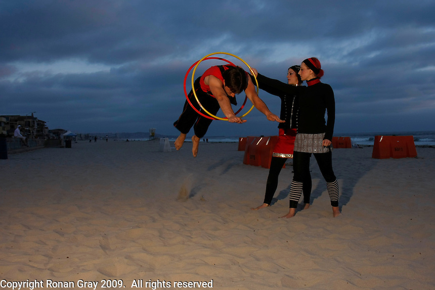 Monday, May 25 2009, San Diego, CA, USA:  Jonathan Nowaczyk dives through a set of hula hoops held by Abigail and ??.